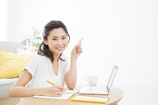 女性がパソコンの前で指をさしてポイントを説明するイメージ